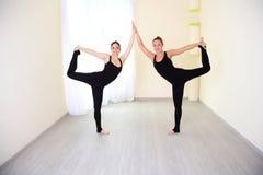 Zwei positive Frauen, gekleidet in übendem Yoga der Sportkleidung Lizenzfreie Stockbilder