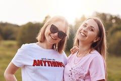 Zwei positive Freundinnen tragen T-Shirt und Schatten, verbringen Freizeit auf Natur, lächeln angenehm an der Kamera, haben gutes Stockfoto
