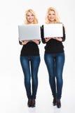 Zwei positive junge blonde Schwestern paart mit Laptop-Computer Stockbilder
