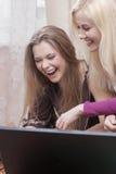 Zwei positive lachende Caucaisan-Freundinnen, die zuhause mit Laptop-Computer arbeiten Lizenzfreie Stockfotografie