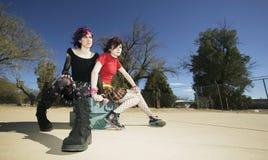 Zwei Punkmädchen, die auf Koffern sitzen Stockfotografie