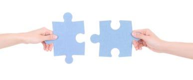 Zwei Puzzlespielstücke in den Frauenhänden lokalisiert auf Weiß stockfotos