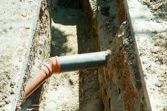 Zwei PVC-Abwasserrohr schloss unterirdisch im Graben auf der Straße an Stockfotografie