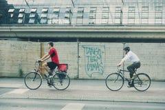 Zwei Radfahrer in der städtischen Umwelt, in tragendem Rot, im anderen in der zufälligen Kleidung des Geschäfts und im Hemd, Berl lizenzfreie stockfotos