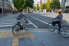 Zwei Radfahrer warten grünes lightat auf Querstraße in Himeji, Kobe, Japan stockfotos