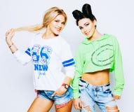 Zwei recht erstaunliche Hippie-Mädchen umarmt und Spaß habend zusammen und trägt modische Kleidung, positive Gefühle, helle Farbe Stockbild