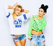 Zwei recht erstaunliche Hippie-Mädchen umarmt und Spaß habend zusammen und trägt modische Kleidung, positive Gefühle, helle Farbe Stockfotos