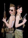 Zwei recht junge Frauen in der Militäruniform mit Gewehren Stockbild