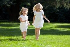 Zwei recht junge Mädchen, die in einen grünen Park laufen Lizenzfreie Stockfotos
