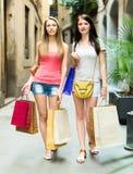 Zwei recht junge Mädchen, die mit Einkaufstaschen gehen Lizenzfreie Stockfotografie