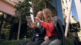 Zwei recht kaukasische junge Mädchen, die nahe Glasgebäude am Sommertag sitzen und etwas auf die Tablette aufpassen stock video