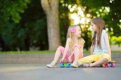 Zwei recht kleine Mädchen, die lernen, am schönen Sommertag in einem Park Skateboard zu fahren Kinder, die Fahrt draußen Skateboa Stockbild