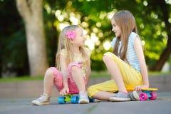 Zwei recht kleine Mädchen, die lernen, am schönen Sommertag in einem Park Skateboard zu fahren Kinder, die Fahrt draußen Skateboa Lizenzfreie Stockbilder