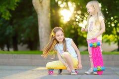 Zwei recht kleine Mädchen, die lernen, am schönen Sommertag in einem Park Skateboard zu fahren Kinder, die Fahrt draußen Skateboa Lizenzfreie Stockfotografie