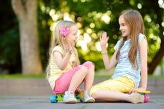 Zwei recht kleine Mädchen, die lernen, am schönen Sommertag in einem Park Skateboard zu fahren Kinder, die Fahrt draußen Skateboa Lizenzfreies Stockfoto