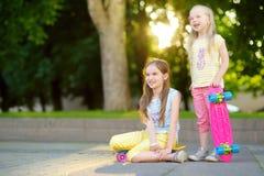 Zwei recht kleine Mädchen, die lernen, am schönen Sommertag in einem Park Skateboard zu fahren Kinder, die Fahrt draußen Skateboa Stockfotos