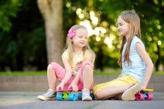 Zwei recht kleine Mädchen, die lernen, am schönen Sommertag in einem Park Skateboard zu fahren Kinder, die Fahrt draußen Skateboa Stockfoto