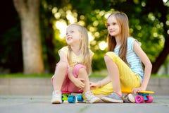 Zwei recht kleine Mädchen, die lernen, am schönen Sommertag in einem Park Skateboard zu fahren Kinder, die Fahrt draußen Skateboa Stockfotografie