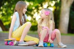 Zwei recht kleine Mädchen, die lernen, am schönen Sommertag in einem Park Skateboard zu fahren Kinder, die Fahrt draußen Skateboa Lizenzfreies Stockbild