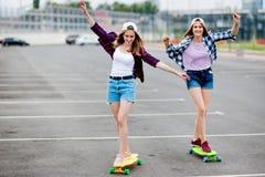 Zwei recht lächelnde blonde Mädchen, die karierte Hemden, Kappen und Denimkurze hosen tragen, longboarding auf dem leeren Parkpla stockbild