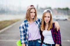 Zwei recht lächelnde blonde Mädchen, die karierte Hemden, Kappen und Denimkurze hosen tragen, stehen auf dem leeren Parkplatz mit stockfotografie