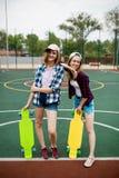 Zwei recht lächelnde blonde Mädchen, die karierte Hemden, Kappen und Denimkurze hosen tragen, stehen auf dem sportsfield mit stockbild