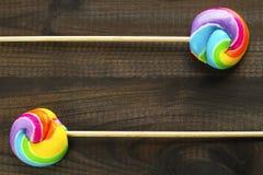 Zwei Regenbogen farbige Lutscher auf blauem hölzernem Hintergrund Stockfoto