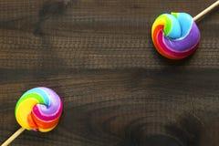 Zwei Regenbogen farbige Lutscher auf blauem hölzernem Hintergrund Stockbilder