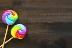 Zwei Regenbogen farbige Lutscher auf blauem hölzernem Hintergrund Stockfotografie