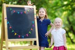 Zwei regten kleine Schwestern durch eine Tafel auf Stockfoto