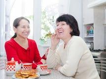 Zwei reife Frauen, die über Küchentisch lachen Lizenzfreie Stockfotografie