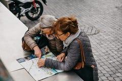 Zwei reife Frauen, die eine Karte betrachten stockfotografie