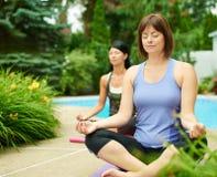 Zwei reife Frauen, die Sitz durch das Handeln von Yoga im Sommer halten Stockfoto