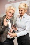 Zwei reife Frauen, die Verordnungslinsen beschließen, um mit neuer Lesebrille zusammenzupassen lizenzfreie stockfotografie