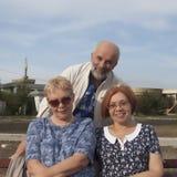 Zwei reife Frauen sitzen auf einer Bank, hinter ihnen ein Mannstand Warmes S stockfotografie