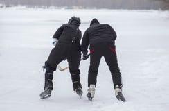 Zwei reife kämpfende Amateurmänner beim Legen des Hockeys auf einen gefrorenen Fluss Dnipro in Ukraine lizenzfreies stockfoto