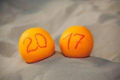 Zwei reife Orangen liegen im Sand auf dem Strand, sie schrieben die Zahl zu Ehren 2017 Lizenzfreie Stockfotos