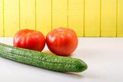 Zwei reife Tomaten und Gurke auf einem hellen Hintergrund gestützt Lizenzfreie Stockfotos