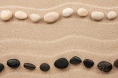 Zwei Reihen von weißen und schwarzen Steinen auf dem Sand Stockfoto
