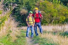 Zwei reisende Kinder mit Rucksäcken Stockfotos