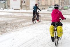Zwei Reitenfahrräder der Leute während des Schneesturms Stockfotos