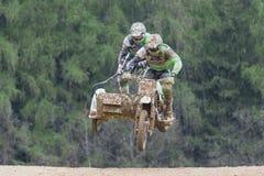 Zwei Reiter springen einen Beiwagen auf dem grünen Hintergrund Stockfoto