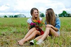Zwei reizend Mädchen, die auf Gras mit sitzen Stockbild