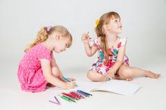 Zwei reizende Mädchen, die mit bunten Bleistiften zeichnen Stockbild