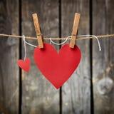 Zwei reizende rote Herzen auf der Wäscheleine Stockfotografie