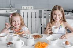 Zwei reizende Schwestern, die gesundes Frühstück essen Lizenzfreie Stockfotografie