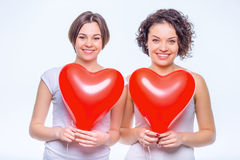 Zwei reizende Schwestern, die mit Ballonen aufwerfen Stockfoto