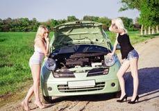 Zwei reizvolle blonde Mädchen stehen das unterbrochene Auto bereit Stockfotos