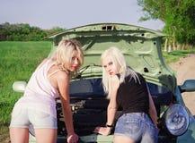 Zwei reizvolle blonde Mädchen stehen das unterbrochene Auto bereit Stockfotografie