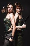 Zwei reizvolle Frauen mit Gewehr und Dolch Stockbild